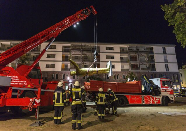 In this Aug. 28, 2018 photo a crane of the firebrigade lifts a statue of Turkish President Recep Tayyip Erdogan in Wiesbaden, western Germany. The statue was part of a controversial art project of the Wiesbaden Biennale