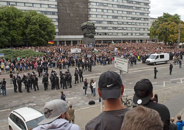 Protesters gather for a far-right protest in front of the Karl Marx Monument in Chemnitz, Germany, Monday, Aug. 27, 2018 after a man has died and two others were injured in an altercation between several people of various nationalities in the eastern German city of Chemnitz on Sunday