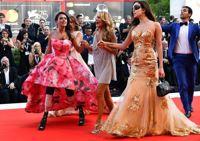 (From L) Paralympic athlete Giusy Versace, Italian singer-songwriter and television presenter, Jo Squillo, and former Miss Italy contestant and TV presenter, who was left scarred after her ex-boyfriend allegedly threw acid in her face, Gessica Notaro arrive for the opening ceremony of the 75th Venice Film Festival, and the premiere of the film First Man, presented in competition at the on August 29, 2018 at Venice Lido
