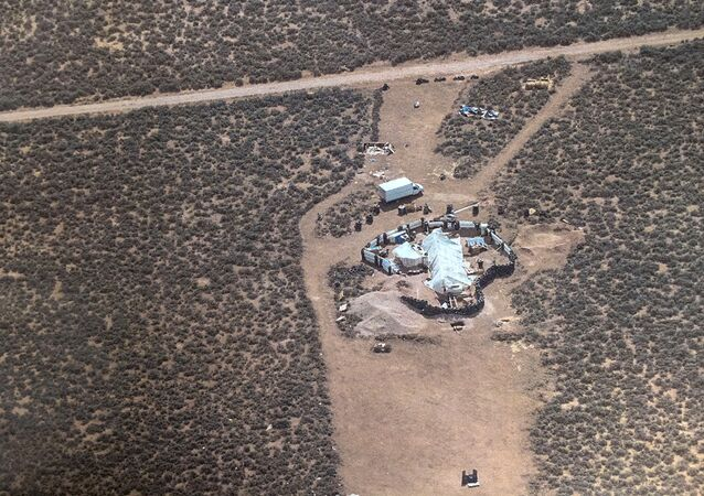 This Friday, Aug. 3, 2018, aerial photo released by Taos County Sheriff's Office shows a rural compound during an unsuccessful search for a missing 3-year-old boy in Amalia, N.M. Law enforcement officers searching the compound for the missing child didn't locate him but found 11 other children in filthy conditions and hardly any food, a sheriff said Saturday.