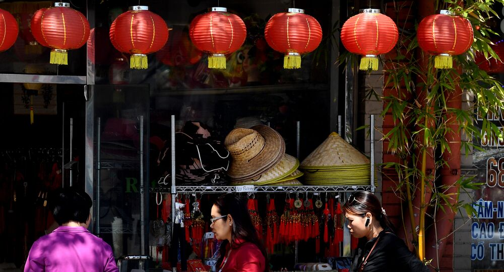 Members of the local Asian community walk on the streets of Chinatown in Los Angeles, California on March 29, 2017.