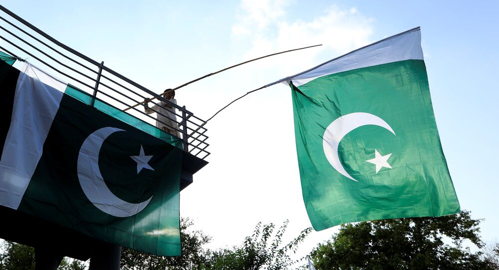 A boy uses a bamboo stick to adjust national flags at an overhead bridge ahead of Pakistan's Independence Day, in Islamabad, Pakistan August 10, 2018