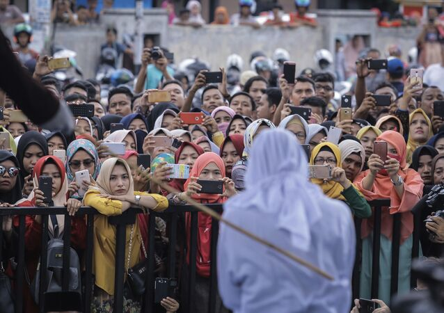 People use their mobile phones to take pictures as a Shariah law official whips a woman who is convicted of prostitution during a public caning outside a mosque in Banda Aceh, Indonesia, Friday, April 20, 2018. Indonesia's deeply conservative Aceh province on Friday caned several unmarried couples for showing affection in public and two women for prostitution before an enthusiastic audience of hundreds. The canings were possibly the last to be carried out before large crowds in Aceh after the province's governor announced earlier this month that the punishments would be moved indoors