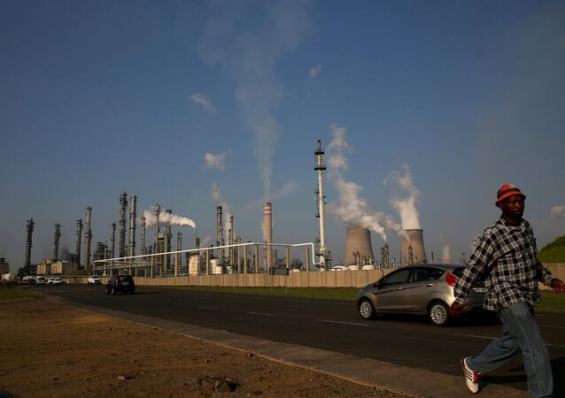 A man walks past South African petrochemical company Sasol's synthetic fuel plant in Secunda, north of Johannesburg (File)