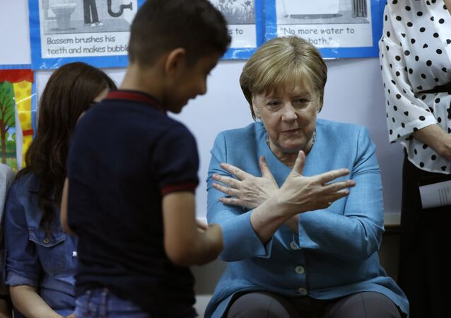 German Chancellor Angela Merkel, right, sits inside a classroom, as she speaks with Lebanese and Syrian displaced students where they studying together, during her visit to a Lebanese public school, in Beirut, Lebanon, Friday, June 22, 2018. Merkel is visiting Jordan and Lebanon, both neighbors of war-torn Syria, amid an escalating domestic row over migration