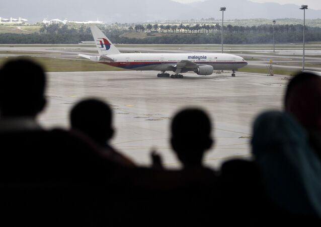 A Malaysian family is silhouetted against a taxied Malaysia Airlines Boeing 777 plane at the Kuala Lumpur International Airport in Sepang, Malaysia, Saturday, March 5, 2016