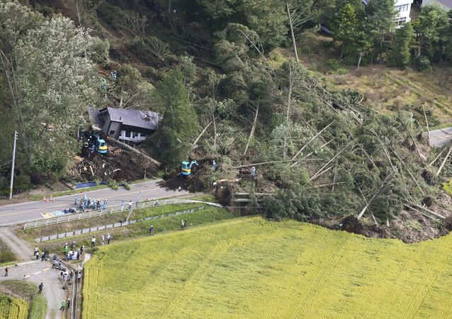 Police officers and rescue workers search for survivors from a building damaged by a landslide caused by a powerful earthquake in Atsuma town in Japan's northern island of Hokkaido, Japan, in this photo taken by Kyodo September 6, 2018.