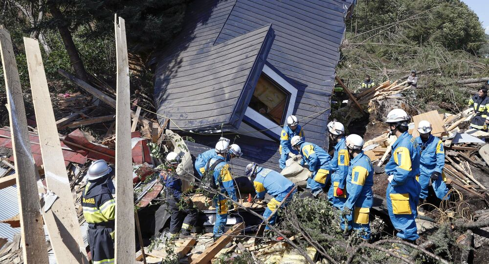 Rescue workers search for survivors from a house damaged by a landslide caused by an earthquake in Atsuma town, Hokkaido, Japan, in this photo taken by Kyodo September 6, 2018