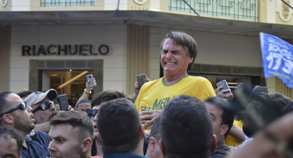 Presidential candidate Jair Bolsonaro grimaces right after being stabbed in the stomach during a campaign rally in Juiz de Fora, Brazil, Thursday, Sept. 6, 2018