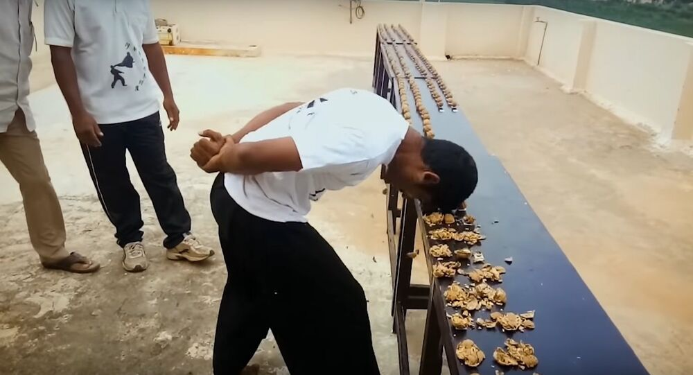 Most walnuts cracked against the head in one minute - Guinness World Records