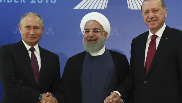 Iran's President Hassan Rouhani, centre, flanked by Russia's President Vladimir Putin, left, and Turkey's President Recep Tayyip Erdogan, pose for photographs in Tehran, Iran, ahead of their summit to discuss Syria, Friday, Sept. 7, 2018 - Sputnik International
