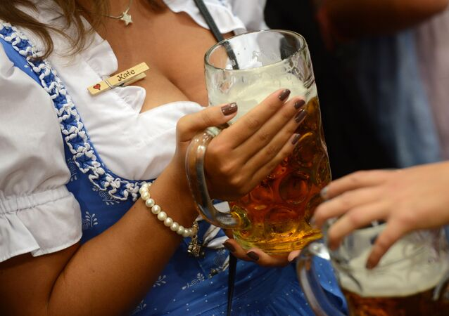 A young woman wearing the Bavarian traditional dress Dirndl holding a beer