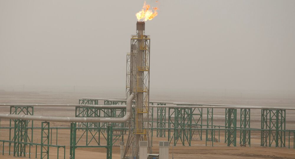 Excess gas is burnt off at a pipeline at the Zubair oilfield in Basra