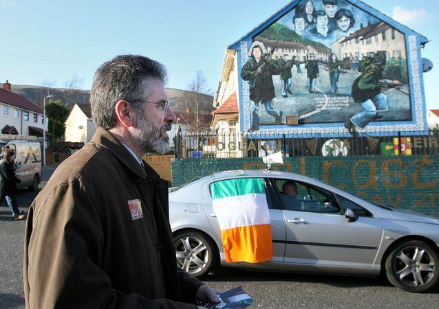 Sinn Fein President Gerry Adams passes a Irish Republican Army mural in the Ballymurphy area of west Belfast , Northern Ireland, Tuesday, March, 6, 2007