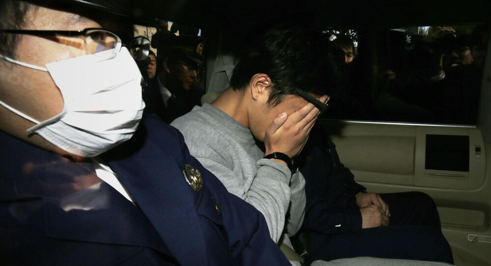 Suspect Takahiro Shiraishi (C) covers his face with his hands as he is transported to the prosecutor's office from a police station in Tokyo on November 1, 2017