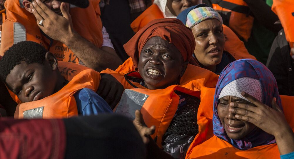 Migrants aboard a rubber dinghy off the Libyan coast receive aid from rescuers aboard the Open Arms aid boat, of Proactiva Open Arms Spanish NGO, Saturday, June 30, 2018.
