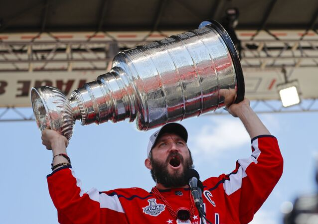 Washington Capitals forward Alex Ovechkin (8), of Russia, holds up the Stanley Cup for fans to see during the NHL hockey team's Stanley Cup victory celebration at the National Mall in Washington, Tuesday, June 12, 2018