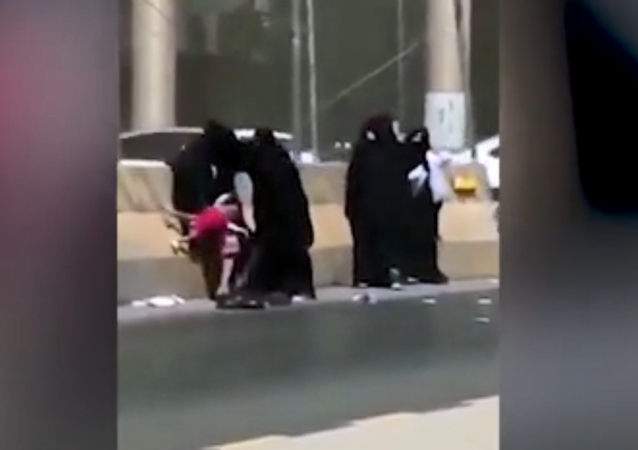 Five Saudi women fight on the side of the road, one with child in tow