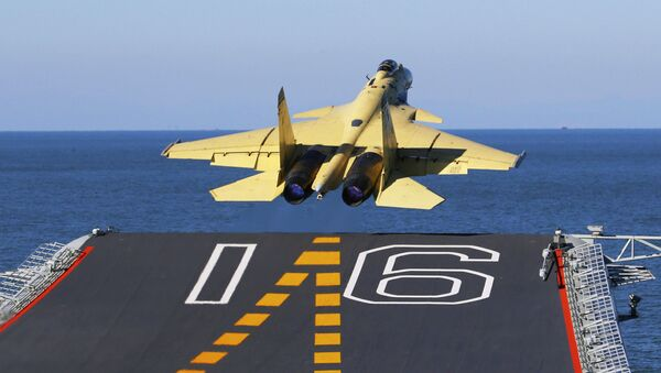 In this undated photo released by China's Xinhua News Agency, made available on Sunday, Nov. 25, 2012, a carrier-borne J-15 fighter jet takes off from China's first aircraft carrier, the Liaoning. China has successfully landed a fighter jet on its first aircraft carrier, which entered service two months ago, the country's official news agency confirmed Sunday. The Liaoning aircraft carrier underscores China's ambitions to be a leading Asian naval power, but it is not expected to carry a full complement of planes or be ready for combat for some time. - Sputnik International