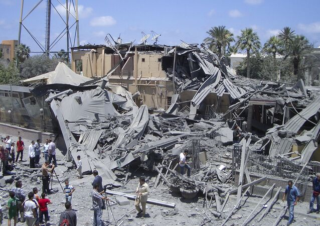 In this photo taken on a government-organized tour, media film damage from what officials said was a NATO airstrike at a hotel, in the capital Tripoli, Libya Thursday, June 16, 2011, while what officials described as a telecommunications tower is seen at left