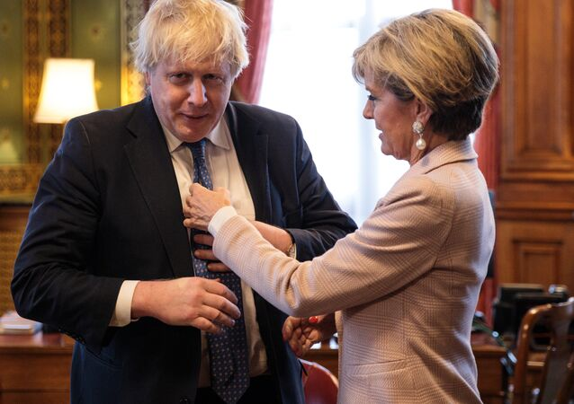 British Foreign Secretary Boris Johnson (L) has his tie straightened by Australian Foreign Minister Julie Bishop (R) at the Foreign and Commonwealth Office in central London on February 23, 2017.