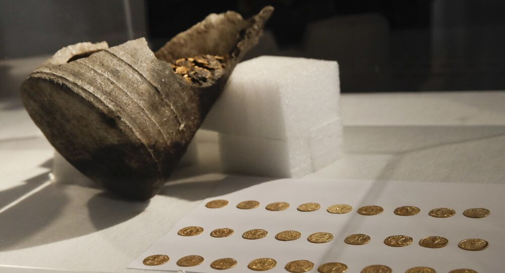 Ancient gold coins are displayed in a plexiglass case during a news conference, in Milan, Italy, Monday, Sept. 10, 2018. Hundreds of gold coins of the late imperial era, kept in a soapstone vessel of uncommon shape were discovered last Wednesday in the center of Como, northern Italy, during restructuring works inside a theater. (AP Photo/Luca Bruno)