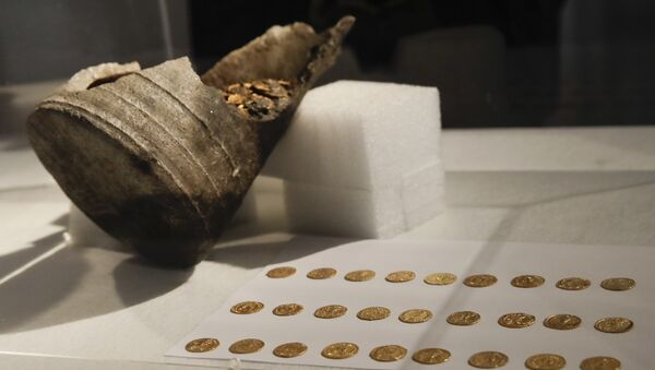 Ancient gold coins are displayed in a plexiglass case during a news conference, in Milan, Italy, Monday, Sept. 10, 2018. Hundreds of gold coins of the late imperial era, kept in a soapstone vessel of uncommon shape were discovered last Wednesday in the center of Como, northern Italy, during restructuring works inside a theater. (AP Photo/Luca Bruno) - Sputnik International