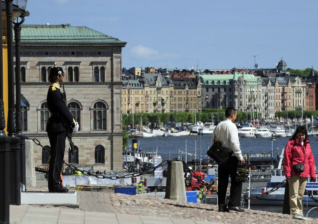 Tourists stand by the Royal Castle (L) in front of a Royal guard in Stockholm (File)