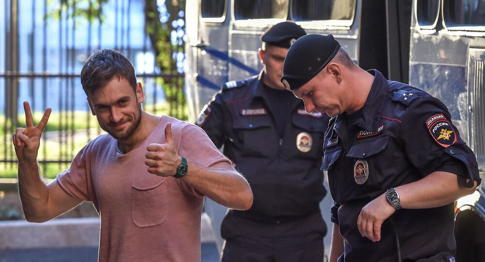 In this file photo taken on July 31, 2018 Member of the Pussy Riot punk group Pyotr Verzilov (L) gestures as he walks with police during a court hearing at a courthouse in Moscow, as members of the Russian protest-art group are accused of disturbing public order after invading the pitch during the World Cup final in Moscow.