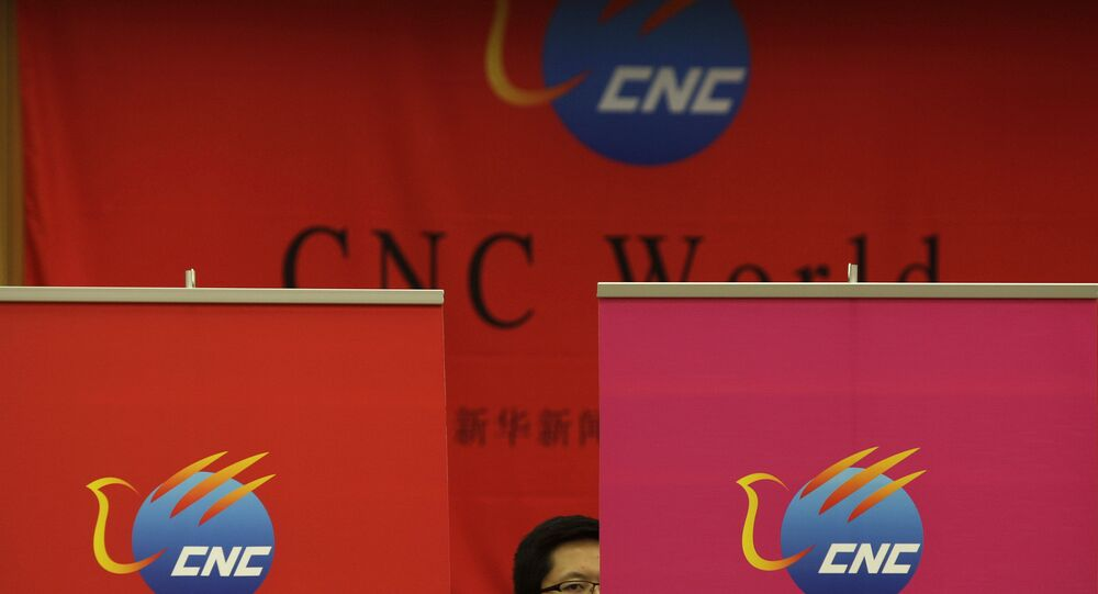 A Chinese employee of China Xinhua News Network Corp. (CNC) looks on during a media conference on the launching of its global, English-language television channel in Beijing Thursday, July 1, 2010.