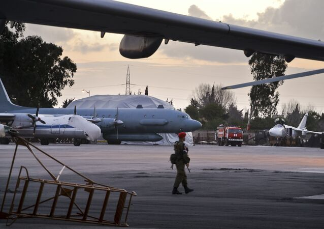 In this photo taken on Friday, March 4, 2016, A Russian military police officer stands guard at the Russian air base in Hemeimeem, Syria, with an Il-20 electronic intelligence plane of the Russian air force is in the background. An Il-20 aircraft was shot down Tuesday, Sept. 18, 2018 by a Syrian missile over the Mediterranean Sea, killing all 15 people on board, as the Syrian military fired on Israeli fighter jets attacking targets in northwestern Syria