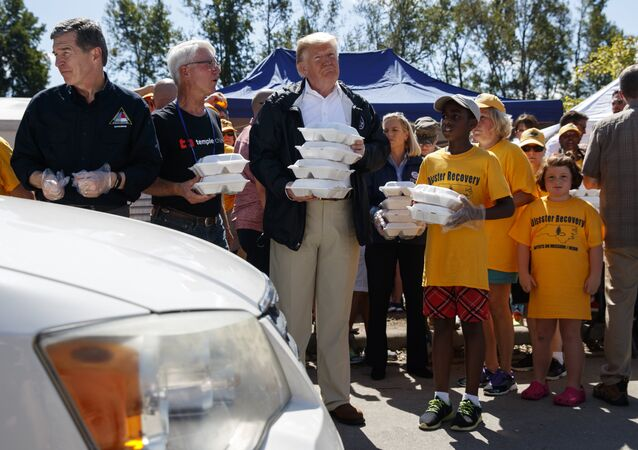 President Donald Trump hands out prepackaged meals to people in cars at Temple Baptist Church in an area impacted by Hurricane Florence.