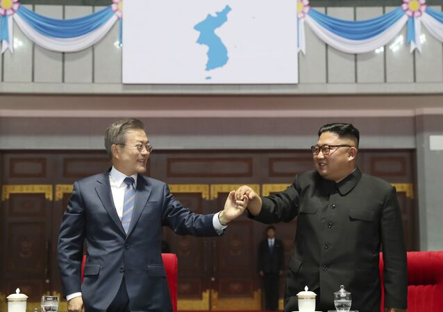 South Korean President Moon Jae-in, left, and North Korean leader Kim Jong Un hold their hands after watching the mass games performance of The Glorious Country at May Day Stadium in Pyongyang, North Korea, Wednesday, Sept. 19, 2018. Unification flag symbol at top centre.