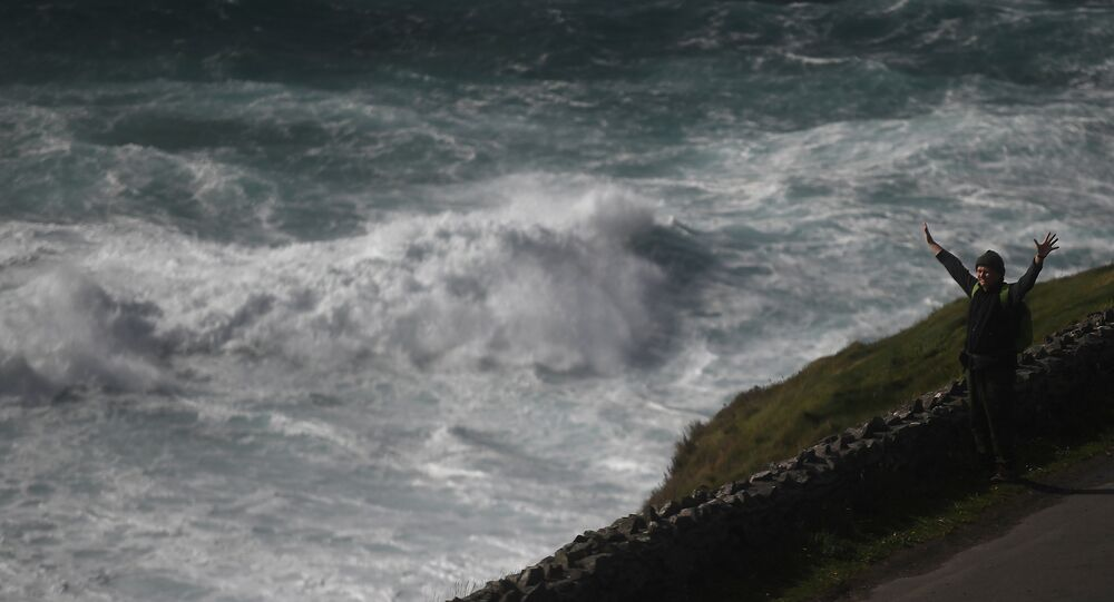 A man looks out at rough sea from Slea Head during Storm Ali in Coumeenoole