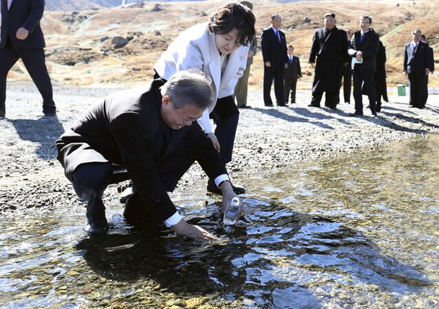 South Korean President Moon Jae-in puts water from the crater lake into a bottle as his wife Kim Jung-sook watches on Mount Paektu