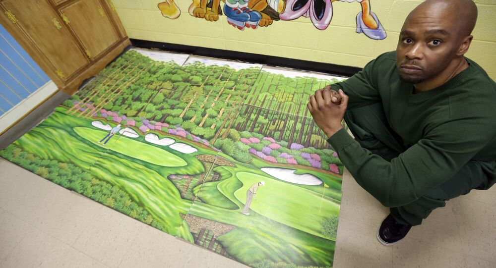Valentino Dixon in prison with one of the hundreds of golf course drawings he created behind bars