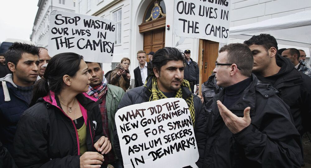 Some thirty Syrian refugees from different camps seeking asylum hold banners outside the Swedish Embassy in Copenhagen, Denmark on Wednesday, Sept. 26, 2012