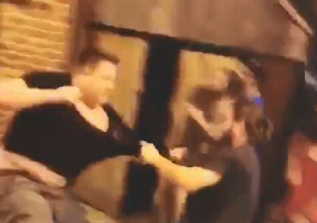 Man in a Proud Boys shirt is confronted by a crowd outside a Kansas City bar