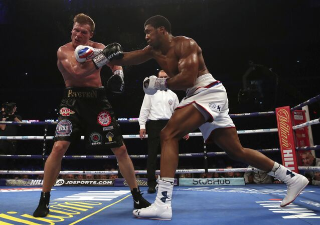 Britain's Anthony Joshua, right, lands a blow on Alexander Povetkin on his way to retaining his WBA, IBF, and WBO heavyweight boxing titles, Saturday, Sept. 22, 2018, at Wembley Stadium in London.