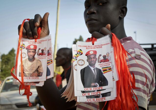 A supporter holds up images of Bobi Wine, a popular Ugandan singer who is now a rising opposition politician