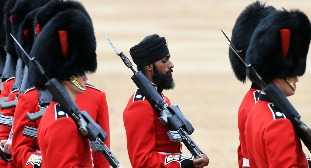 A Sikh member of the Coldstream Guards, center, wears a turban as he takes part in the Colonel's Review, the final rehearsal for Trooping the Colour, the Queen's annual birthday parade, in London, Saturday, June 2, 2018.