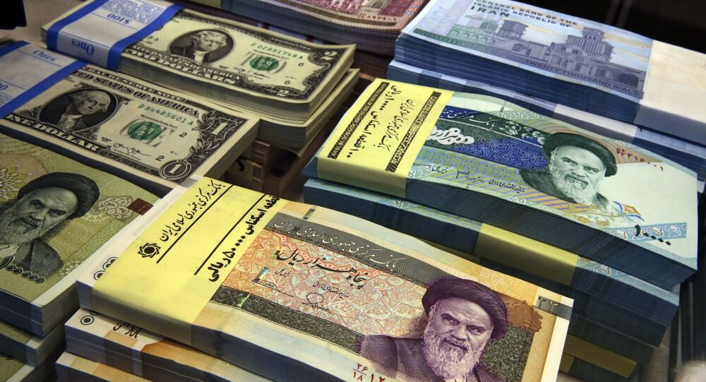 In this April 4, 2015 file photo, Iranian and U.S. banknotes are on display at a currency exchange shop in downtown Tehran, Iran