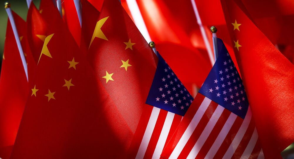In this Sept. 16, 2018, photo, American flags are displayed together with Chinese flags on top of a trishaw in Beijing. The American Chamber of Commerce in China says Beijing will dig its heels in after U.S. tariff hikes and appealed for a negotiated end to their trade battle