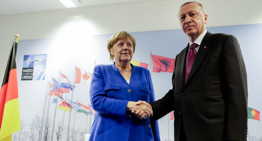 German Chancellor Angela Merkel, left, and Turkish President Recep Tayyip Erdogan, right, shake hands prior to a bilateral meeting on the sideline of a summit of heads of state and government at NATO headquarters in Brussels Wednesday, July 11, 2018