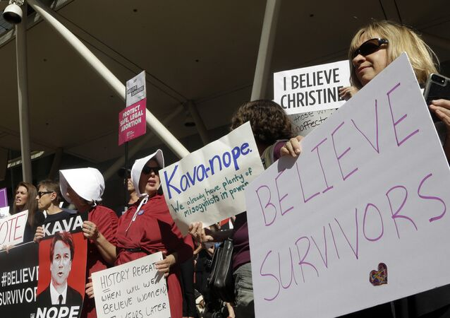 Protestors hold signs during a demonstration against the nomination of Brett Kavanaugh to sit on the U.S. Supreme Court in Portland, Ore., Friday, Sept. 28, 2018