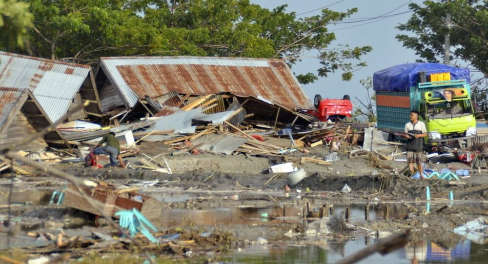 A man stands amid the damage caused by a tsunami in Palu, Central Sulawesi, Indonesia, Saturday, Sept. 29, 2018. A powerful earthquake rocked the Indonesian island of Sulawesi on Friday, triggering a 3-meter-tall (10-foot-tall) tsunami that an official said swept away houses in at least two cities.