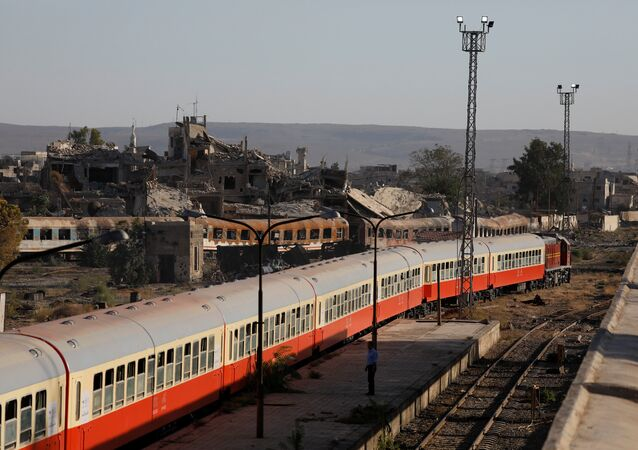 Damaged buildings are seen next a railway station in Damascus