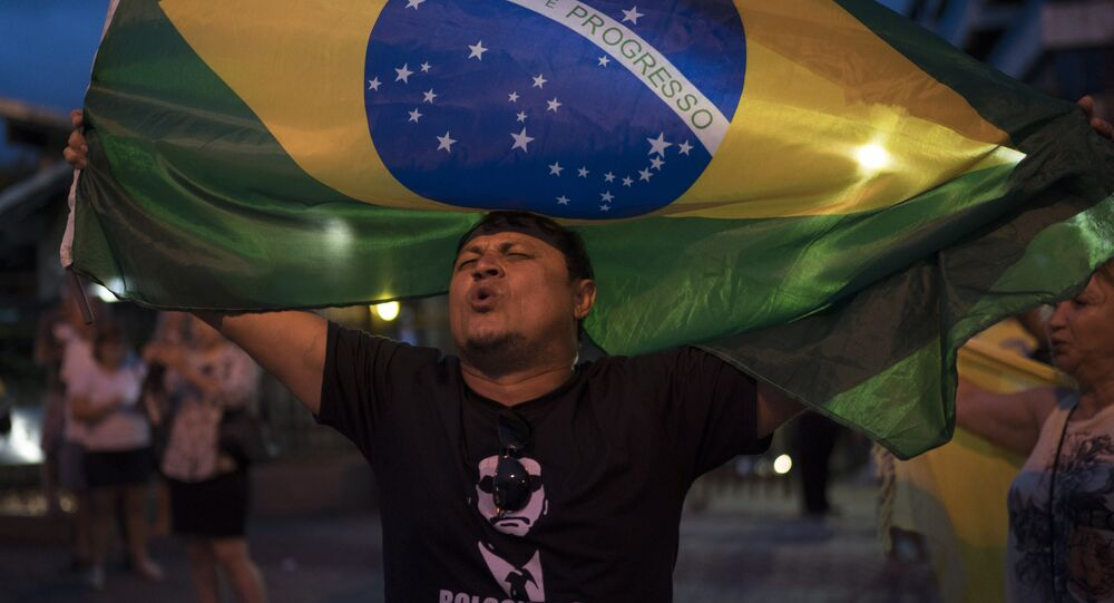 A man sings the Brazil's national anthem as he waves the national flag in support leading presidential candidate Jair Bolsonaro, outside Bolsonaro's residence in Rio de Janeiro, Brazil