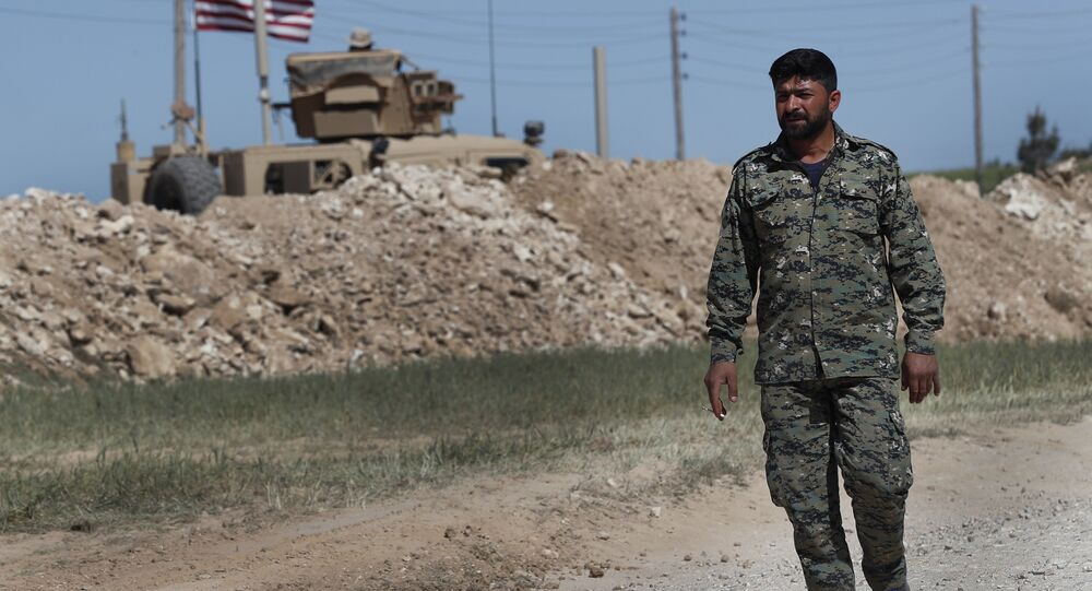 In this April 4, 2018 file photo, a U.S-backed Syrian Manbij Military Council soldier passes a U.S. position near the tense front line with Turkish-backed fighters, in Manbij, north Syria