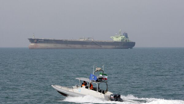 In this July 2, 2012 file photo, an Iranian Revolutionary Guard speedboat moves in the Persian Gulf while an oil tanker is seen in background - Sputnik International
